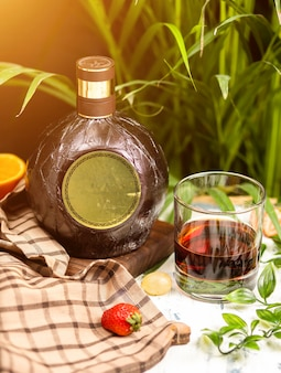 Wineglass and traditional round bottle on a wooden board on kitchen table. with check tablecloth, fruits and herbs around.