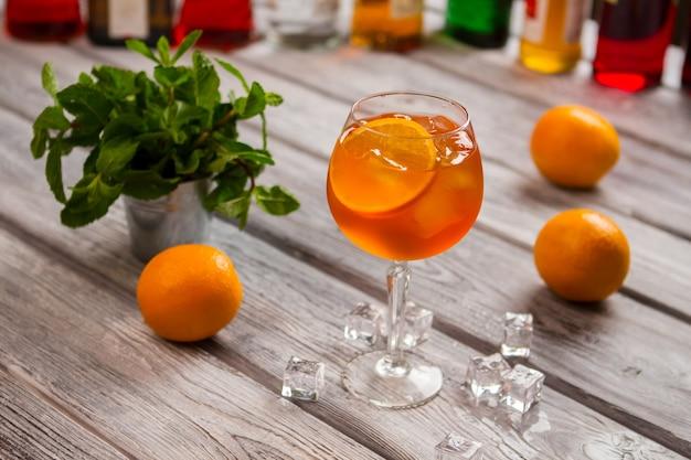 오렌지 칵테일과 와인 글라스입니다. 작은 양동이에 민트. 오렌지 슬라이스를 곁들인 아페롤 스프릿츠. 긴장을 풀고 음료를 즐기십시오.