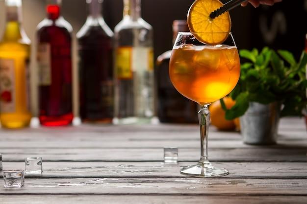 오렌지 음료와 함께 와인 글라스입니다. 집게는 오렌지 조각을 들고 있습니다. 바에서 제공되는 aperol spritz. 탄산수와 스파클링 와인.