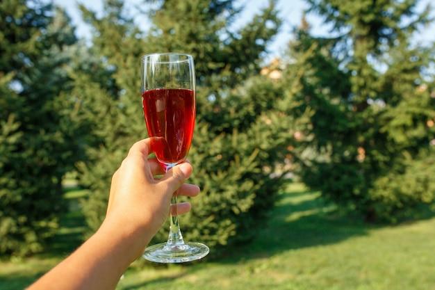 Рюмка с красным шампанским стоять на деревянном столе в зеленом парке летом