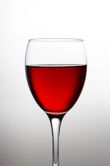 Wineglass with red wine close-up isolated on light gradient
