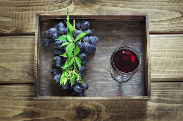 Wineglass with red wine and ripe grape on wooden board.