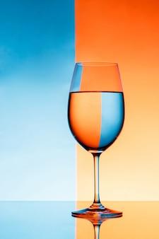 Bicchiere da vino con acqua sopra la parete blu e arancione