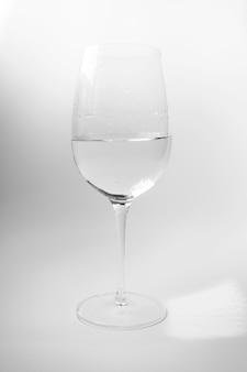 Рюмка с водой на белой стене. элеганс роскошный безалкогольный напиток