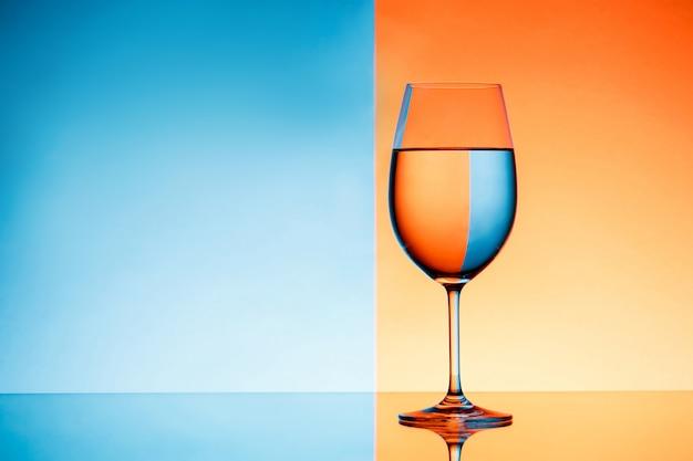 Рюмка с водой на синий и оранжевый фон.
