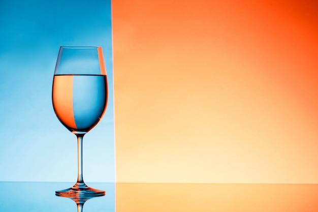 青とオレンジ色の背景上の水でワイングラス。