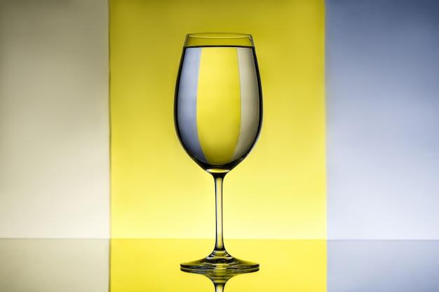 灰色と黄色の背景の上の水でワイングラス。