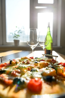 ワイングラスのワインと新鮮な焼きピザ