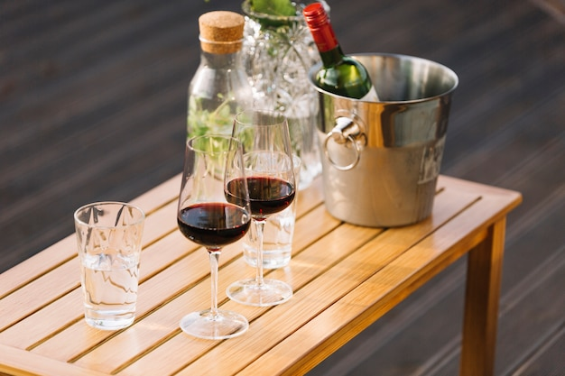 Wineglasses and ice bucket with wine bottle on small wooden table