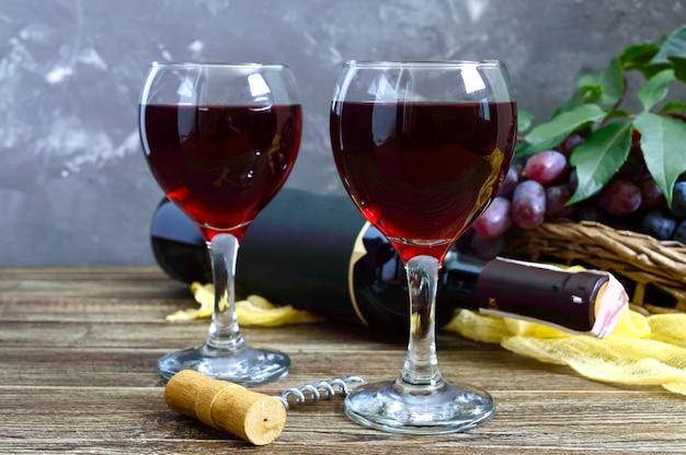 Бокалы с красным вином, бутылка и свежий виноград
