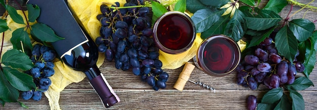 Wineglasses with red wine, bottle, corkscrew, blue grapes, leaves on a wooden table. wine background with copy space. top view, flat lay. banner