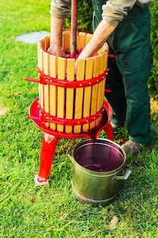 Winepress machine.young man making wine using wooden winepress machine. crusher on grass outdoors. grape harvest. concept of small craft business. special equipment for production of wine, winemaking.