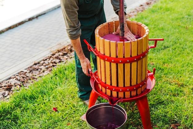 포도주 프레스 기계입니다. 나무로 되는 포도주 프레스 기계를 사용하여 포도주를 만드는 청년. 야외 잔디에 크러셔입니다. 포도 수확. 작은 공예 사업의 개념입니다. 와인 생산, 포도주 양조를 위한 특수 장비. 프리미엄 사진