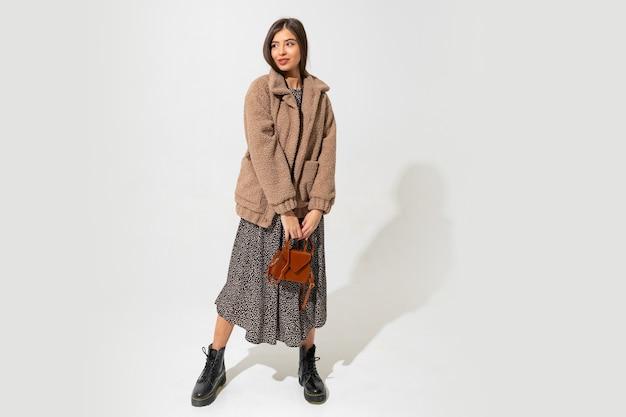 勝者のファッションルック。ベージュのファーコートを着たスタイリッシュなブルネットモデルと。全長。