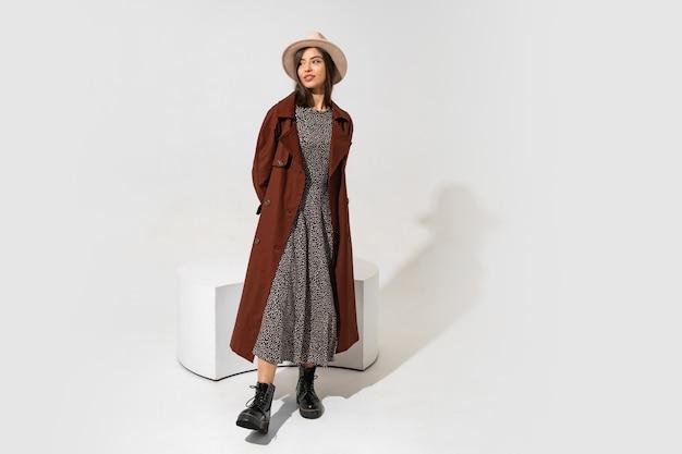 勝者のファッションルック。茶色のコートと黒革のポーズでアンクルブーツのスタイリッシュなブルネットモデル