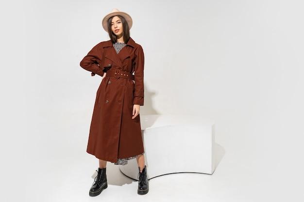위너 패션 룩. 갈색 코트와 베이지 색 모자 포즈에 세련된 갈색 머리 모델