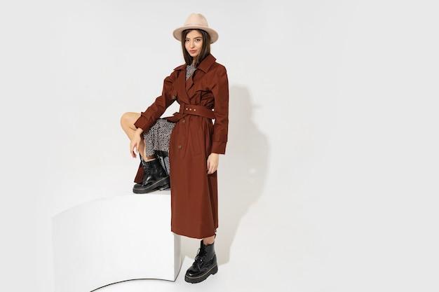 Модный образ winer. стильная брюнетка-модель в коричневом пальто и бежевой шляпе позирует