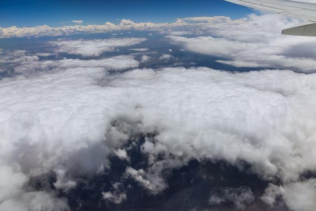 구름 위를 비행하는 비행기 중 고도의 날개 항공기