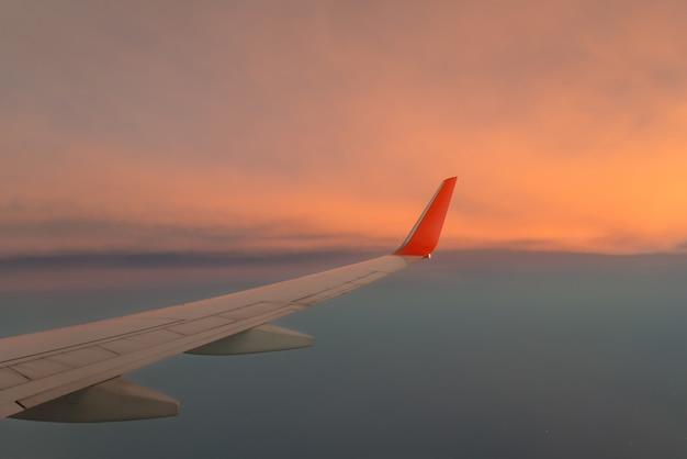 Wing airplane against the sunset sky above the cloud.