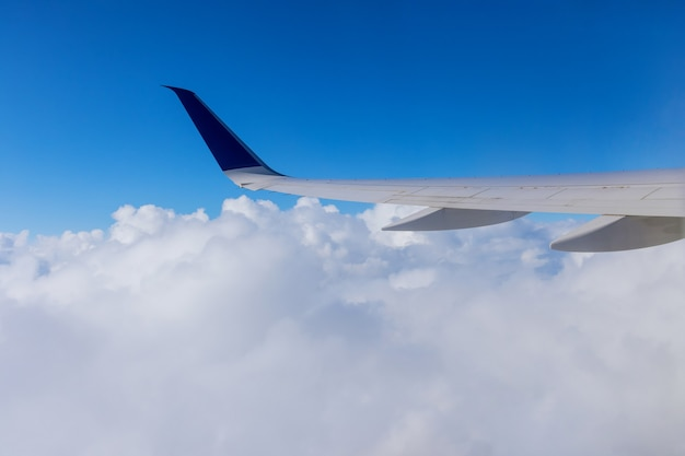 Wing of an airplane flying above the clouds of an aircraft