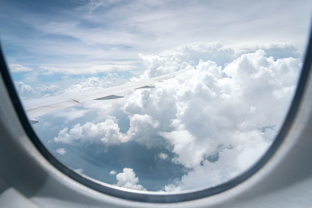 Wing of airplane flying above the clouds in the blue sky background through the window.