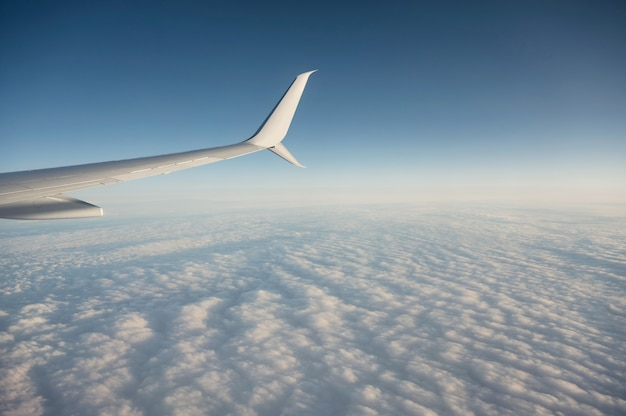 Wing of airplane flying over cloudy in the blue sky