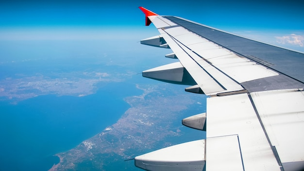 Wing of the airplane flying above land and ocean.