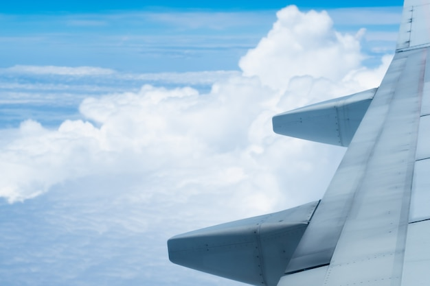 Wing of an airplane with beautiful blue sky and clouds background , view from the airplane window.