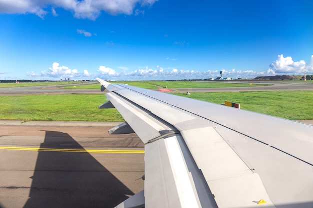 Wing from window of airplane view during plane landing or before takeoff