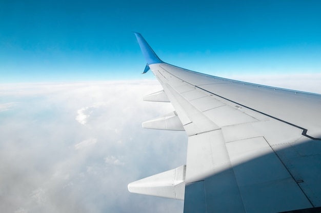 A wing of a modern passenger airplane above the clouds. international cargo transportation, air travel, transport. copy space.