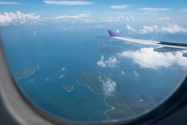창을 통해 홍콩 도시 배경 위에 도착하는 비행기의 날개.