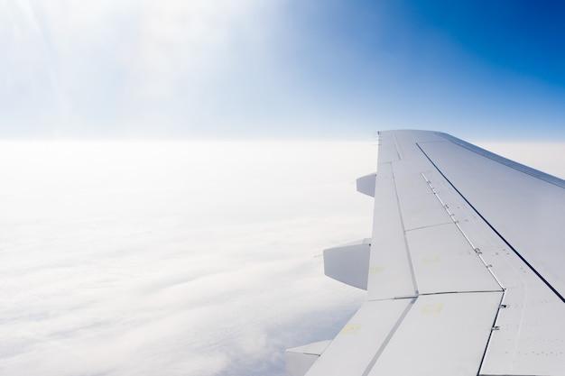 高高度で雲の上を飛んでいる飛行機の翼。旅行、高所恐怖症の概念。コピースペース。