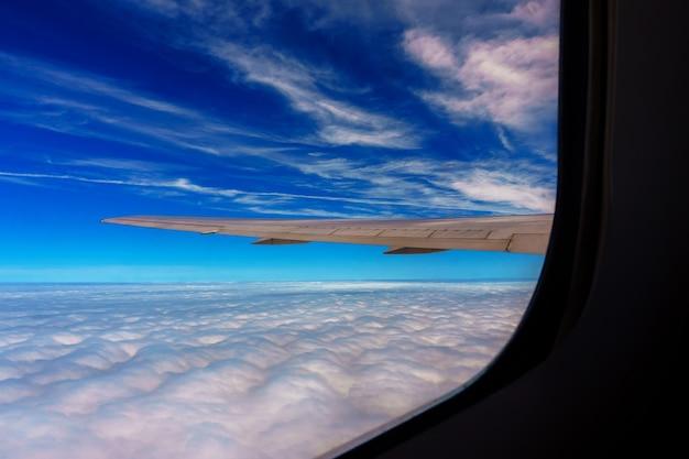 Крыло самолета, летящего над облаками в небе