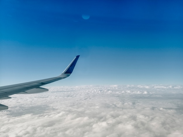 Крыло самолета на белых облаках
