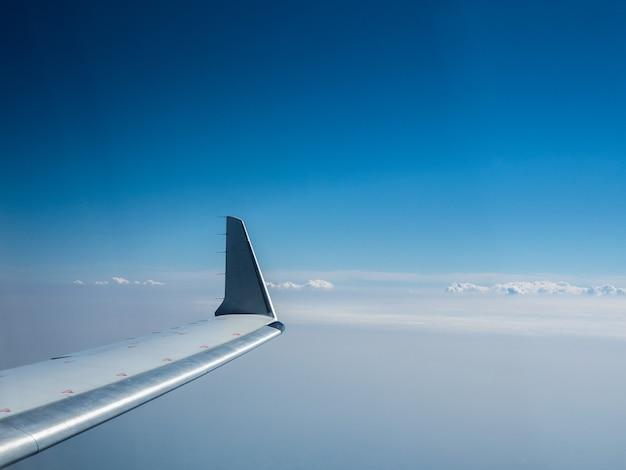 구름 위를 비행하는 비행기의 날개. 비행기 창에서 하늘을 볼 수 있습니다.