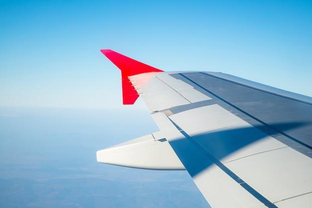 朝の雲の上を飛んでいる飛行機の翼。