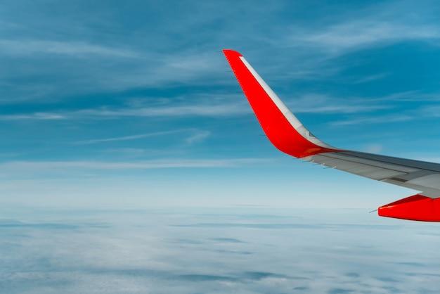 白い雲の上を飛んでいる飛行機の翼