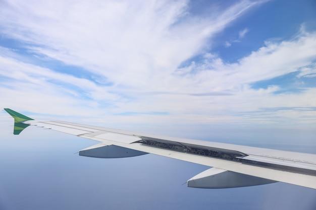 美しい空の雲のある飛行機の翼