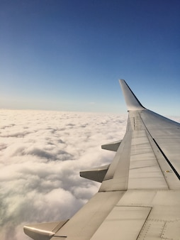 The wing of the plane at a height during the flight of the clouds in the background snapshot