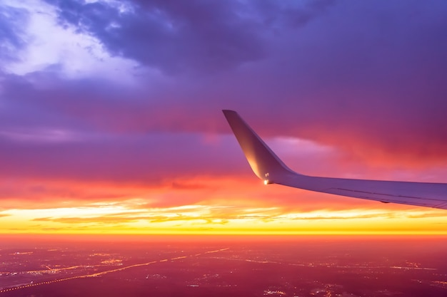 Wing of the plane lit by the sunset on a coloful sky.