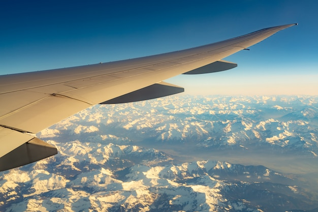 Wing of plane over mountain cover with white snow. airplane flying on blue sky. scenic view from airplane window. commercial airline flight. plane wing. flight mechanics concept.