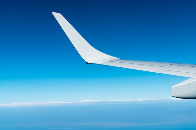 Wing of plane over white clouds. airplane flying on blue sky. scenic view from airplane window. commercial airline flight. plane wing above clouds.