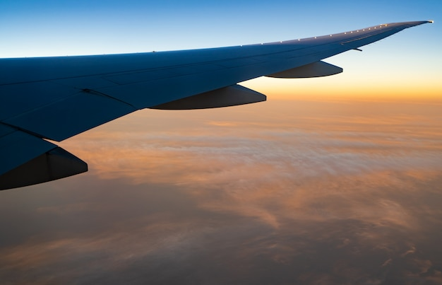 Wing of plane over white clouds. airplane flying on sunrise sky. scenic view from airplane window. commercial airline flight. plane wing above clouds.