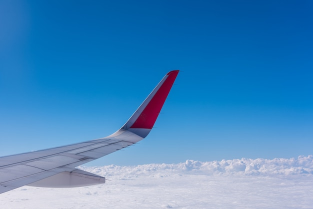 Wing of plane with blue sky and cloud