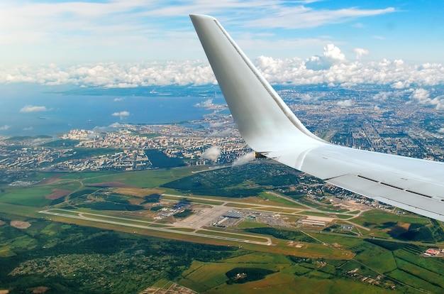 비행기 창에서 날개, 공항, 바다, 도시 및 구름까지 날개 전망.