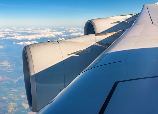 Wing with engines of airbus airliner flying over clouds