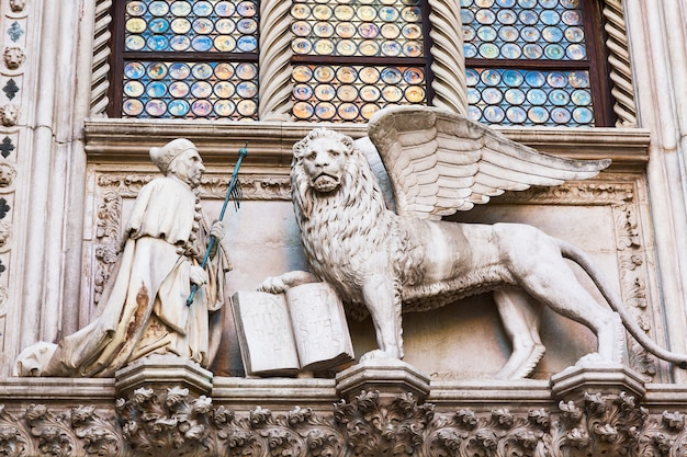 Winged lion and a priest, detail of the doge's palace palazzo ducale in venice, italy,