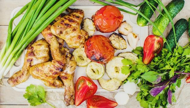 Крылья и овощи на гриле. выборочный фокус.