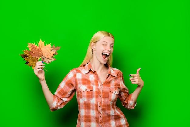 Winking blond woman with gold leaf autumn clothes color trends autumn sale autumnal vogue trend