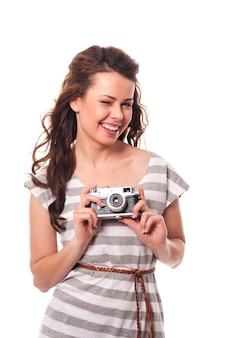 レトロなカメラを保持しているまばたきの女性